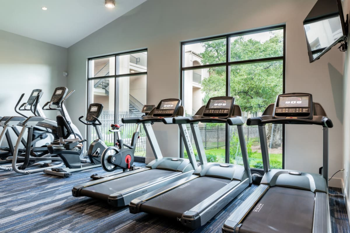 Treadmills, ellipticals, and bike machines in fitness room at Marquis at Great Hills in Austin, Texas