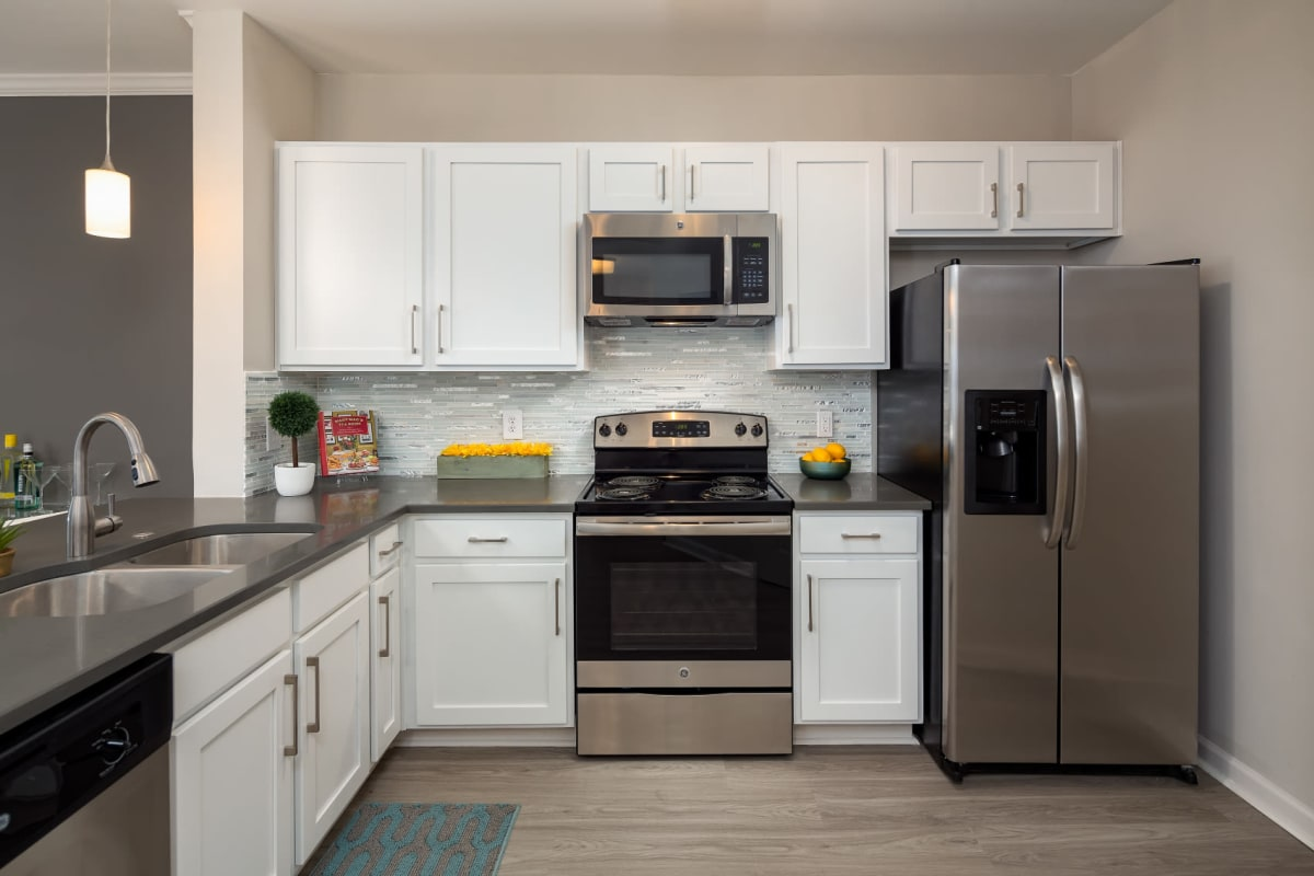 Bright and modern kitchen with stainless steel appliances, white cabinets, and tiled backsplash at Marq on Ponce in Atlanta, Georgia
