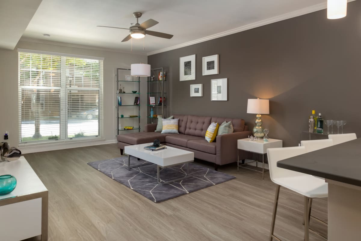 Modern and bright living room with sectional sofa, coffee and side tables, and large window with street view at Marq on Ponce in Atlanta, Georgia