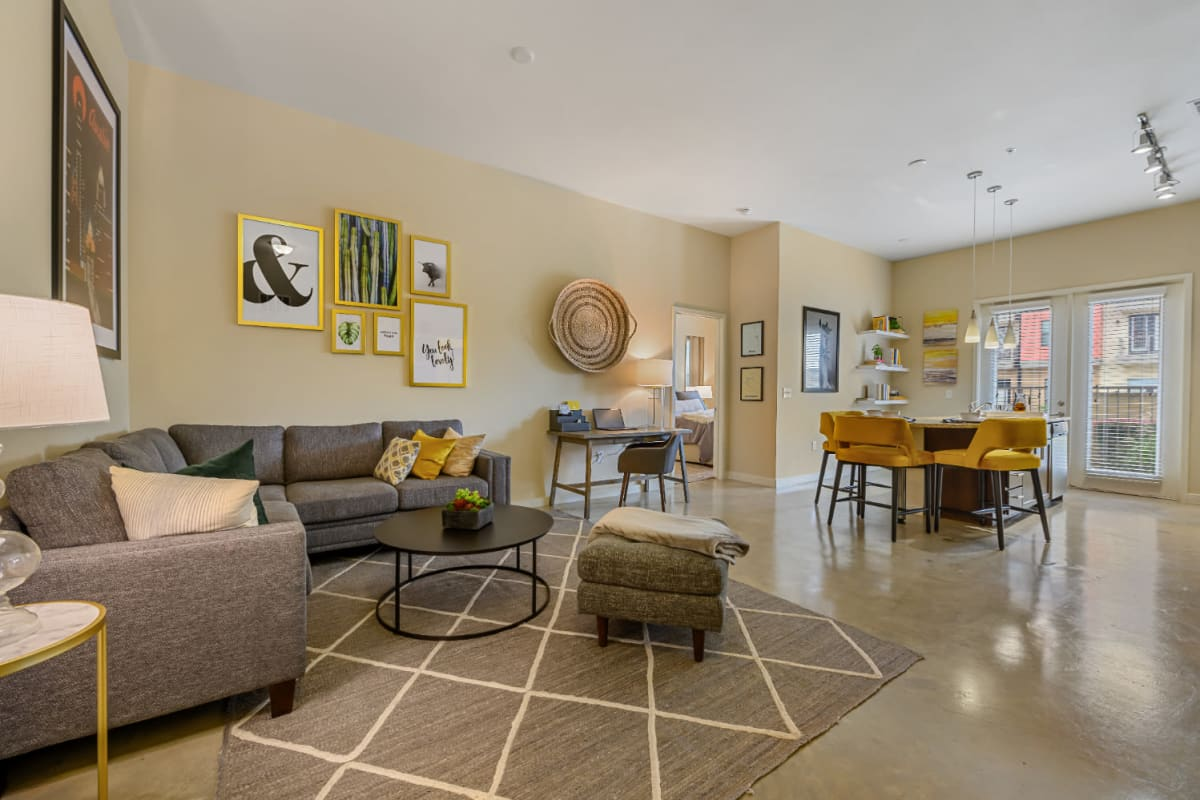 Sectional sofa, work desk, and dining table in open living floor plan at The 704 in Austin, Texas