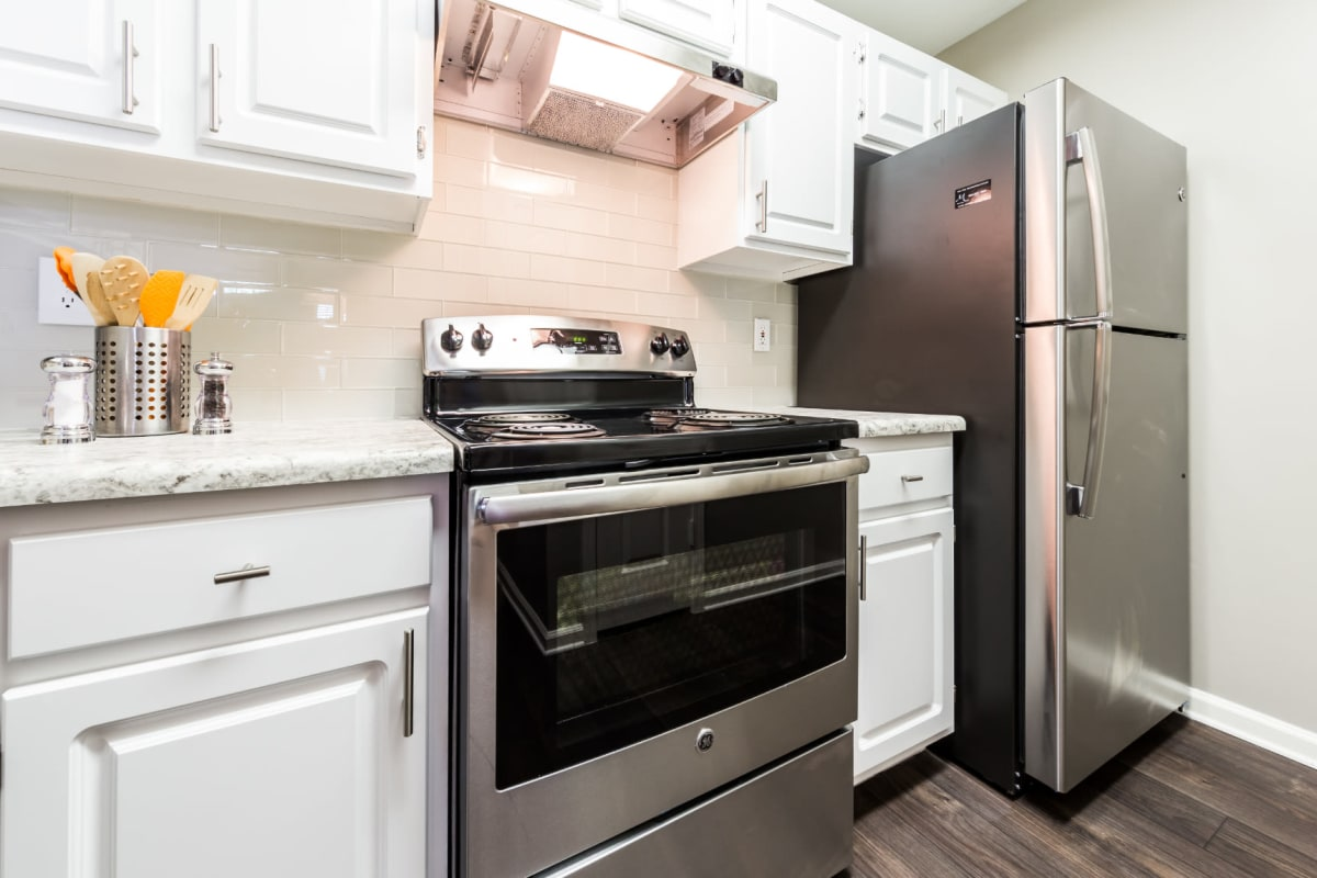 Stainless steel appliances set in white cabinets with granite countertops at The Marq at Brookhaven in Atlanta, Georgia