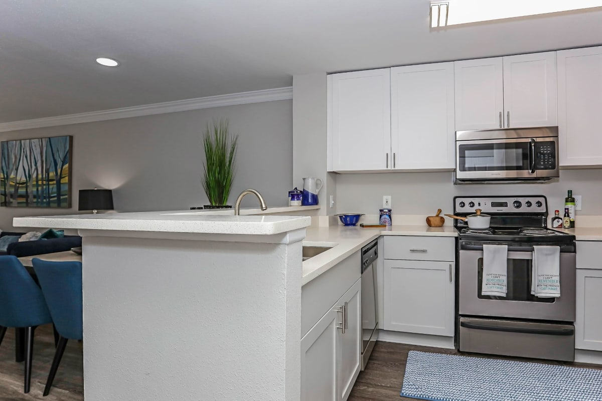 Large kitchen with nice white cabinets and wood style flooring at 45Eighty Dunwoody Apartment Homes in Dunwoody, Georgia