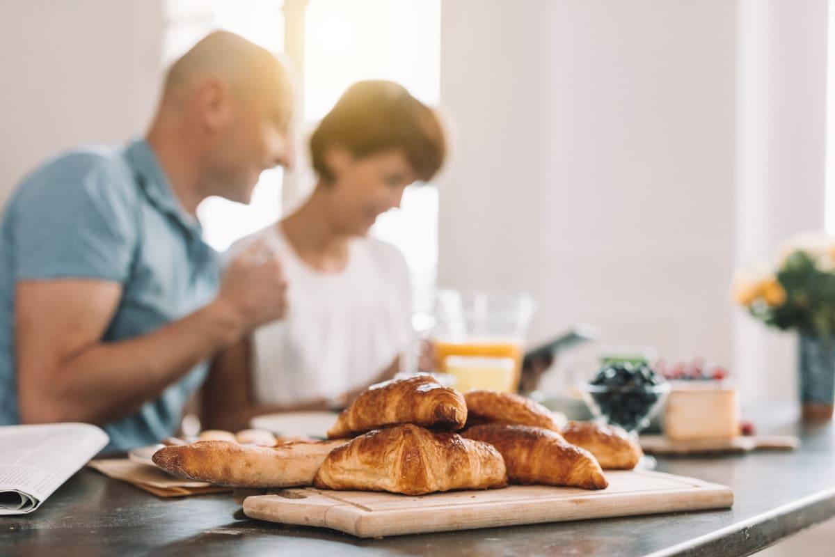 Couple enjoying a leisurely breakfast in their modern kitchen at The Pointe at Siena Ridge in Davenport, Florida