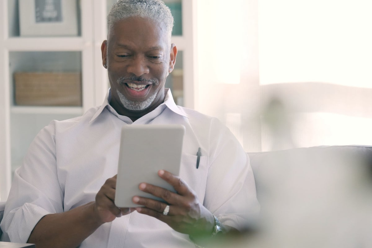 Happy resident checking the news on a tablet device in his new apartment at The Pointe at Siena Ridge in Davenport, Florida
