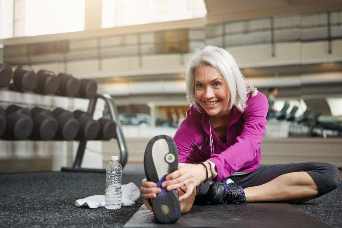 Resident stretching before her workout in the onsite fitness center at The Pointe at Siena Ridge in Davenport, Florida