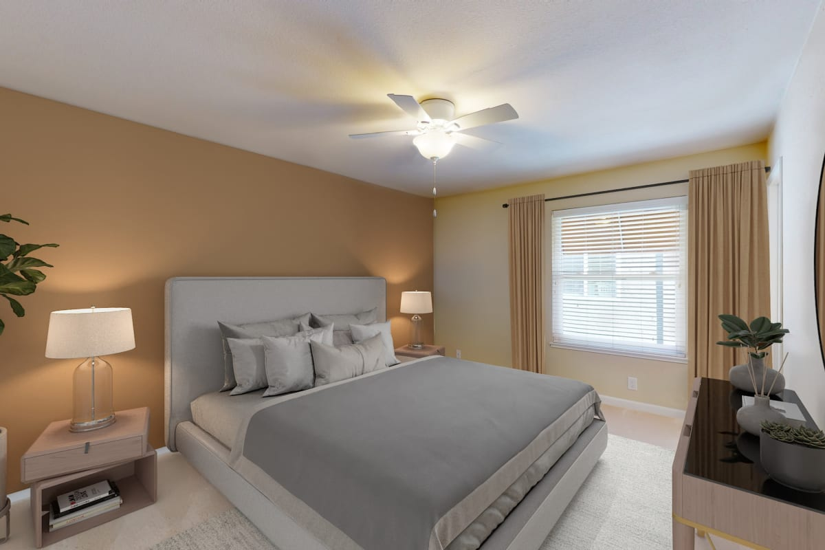 Model home's primary bedroom with a ceiling fan and plush carpeting at Valley Plaza Villages in Pleasanton, California