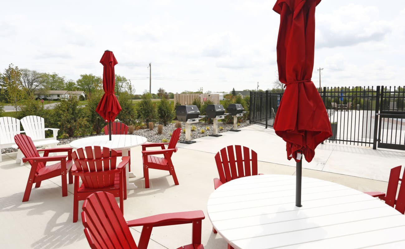 Picnic area with tables and lounge chairs at Bonterra Apartments in Fort Wayne, Indiana