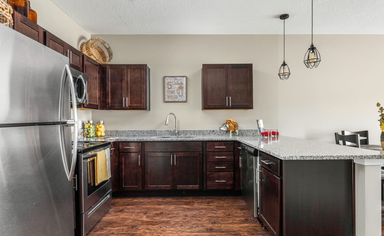 Modern kitchen with stainless-steel appliances and hardwood flooring in a model home at Bonterra Apartments in Fort Wayne, Indiana