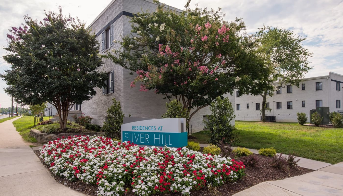Exterior view of resident building at The Residences at Silver Hill with sign in front surrounded by flowers in Suitland, MD