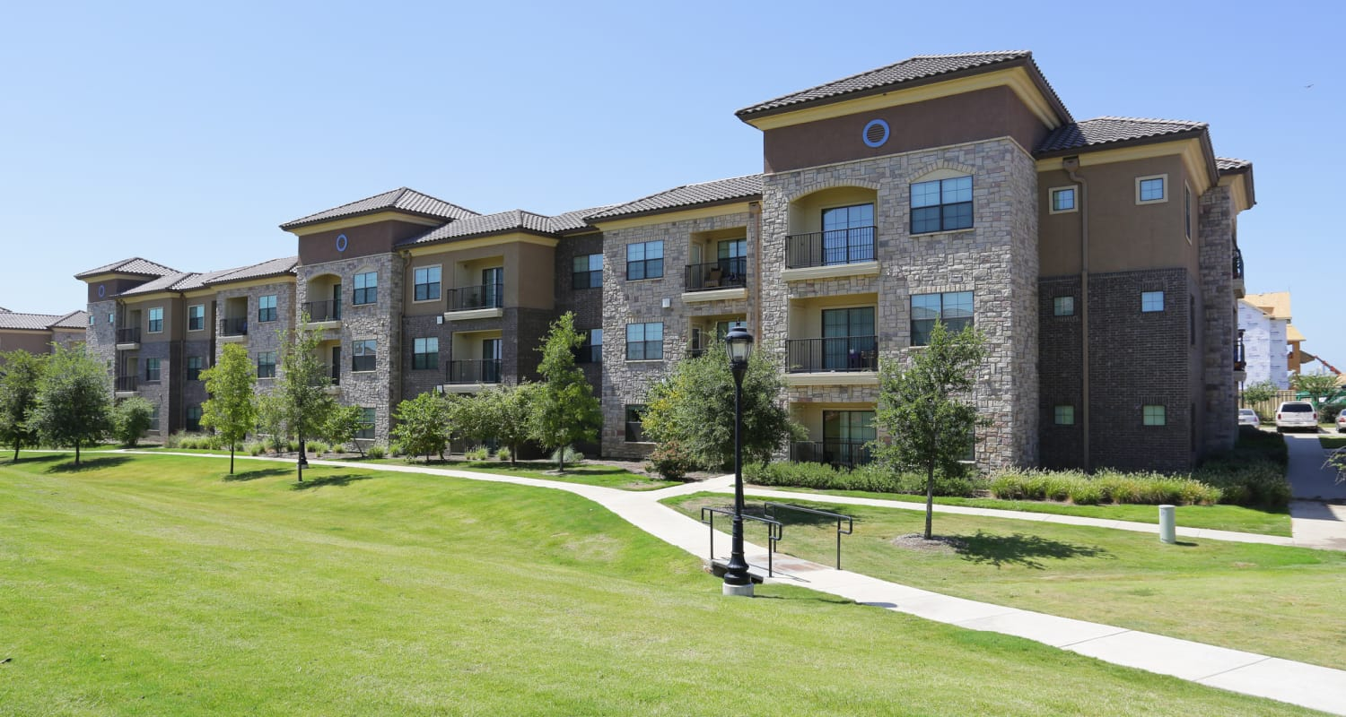 Exterior view of resident buildings and beautifully maintained lawn at Evolv in Mansfield, Texas