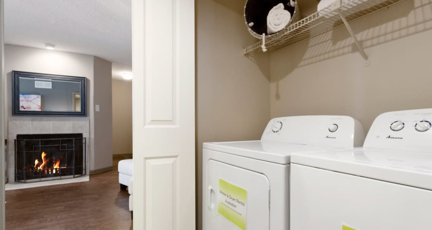 Washer, dryer and fireplace view at Ridgeview Place in Irving, Texas