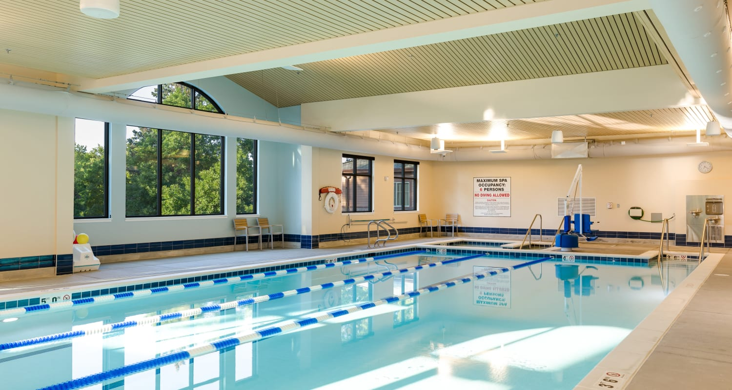 The community pool with a beautiful view of trees outside at Touchmark at All Saints Health & Fitness Club in Sioux Falls, South Dakota