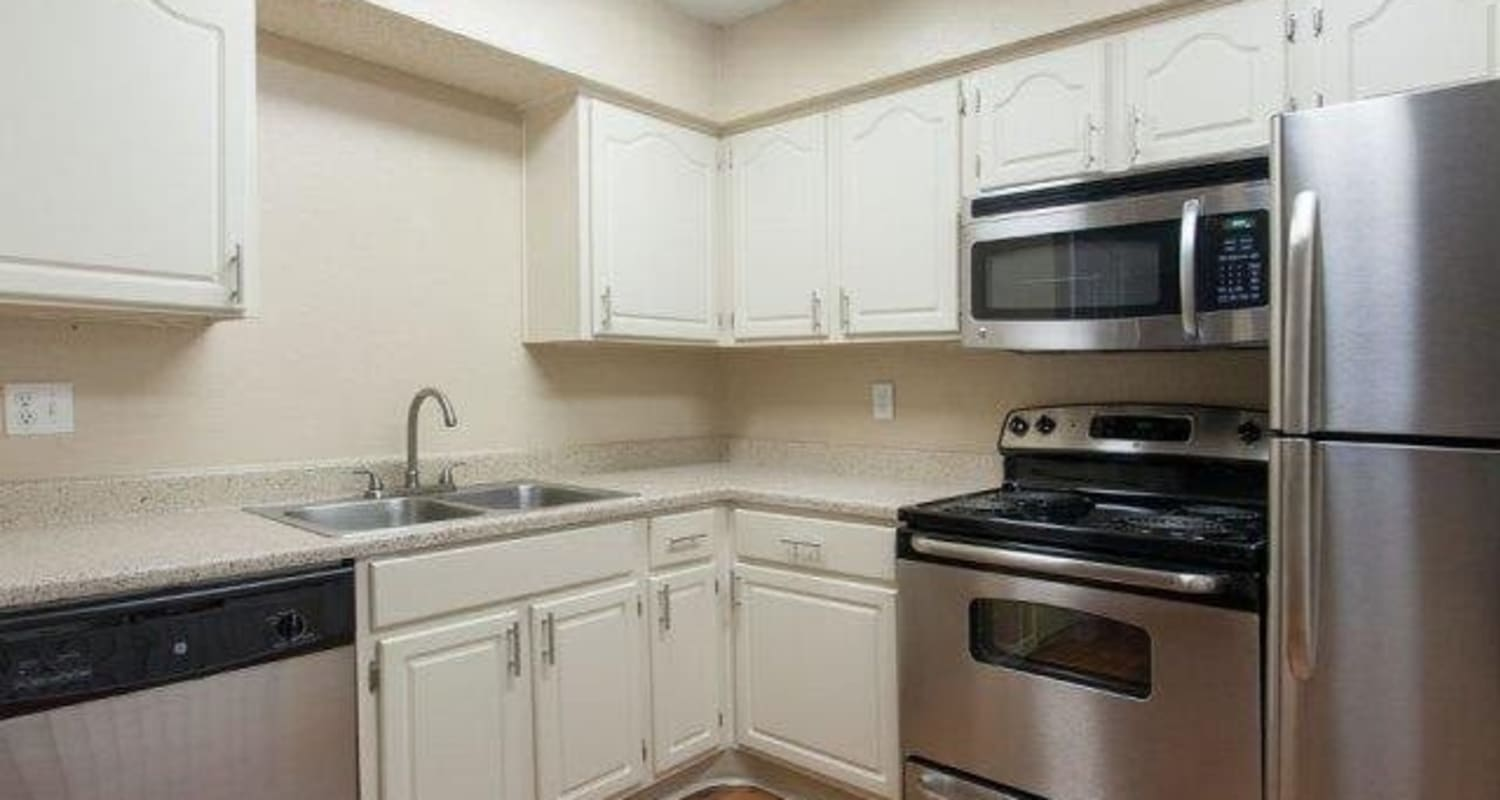 Spacious kitchen with stainless-steel appliances and white cabinetry at The Regent in Dallas, Texas
