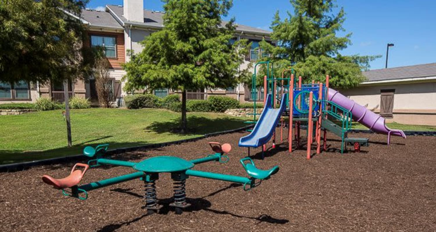 Outdoor children's playground with a seesaw, jungle gym, and slides at Ranch ThreeOFive in Arlington, Texas