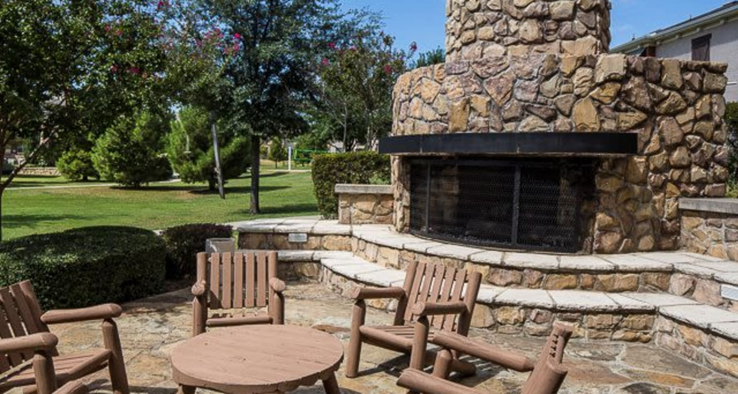 Outdoor patio with table and chairs and a large stone-built fireplace at Ranch ThreeOFive in Arlington, Texas
