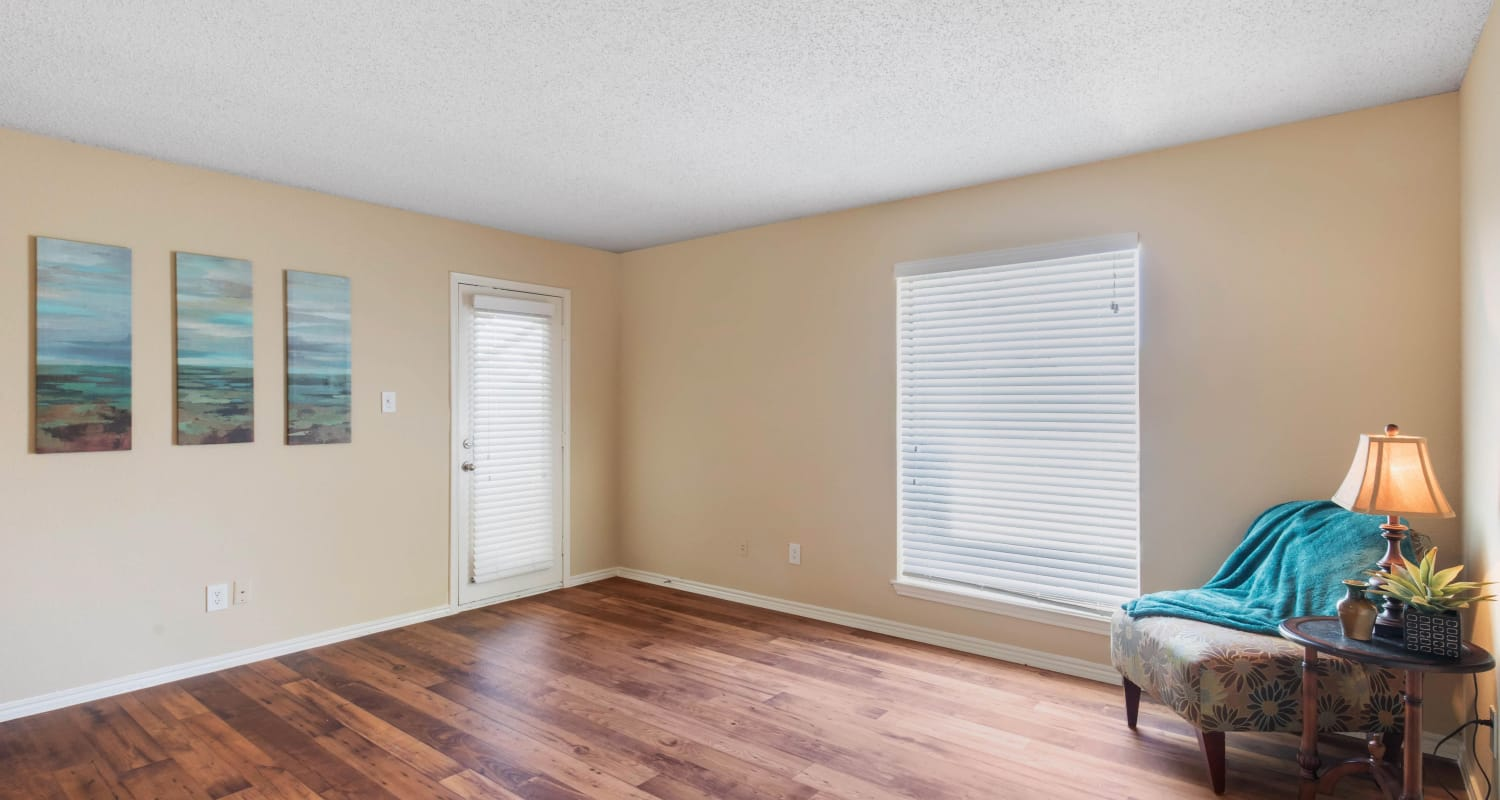 Large living with wood-style flooring at The Logan in Bedford, Texas