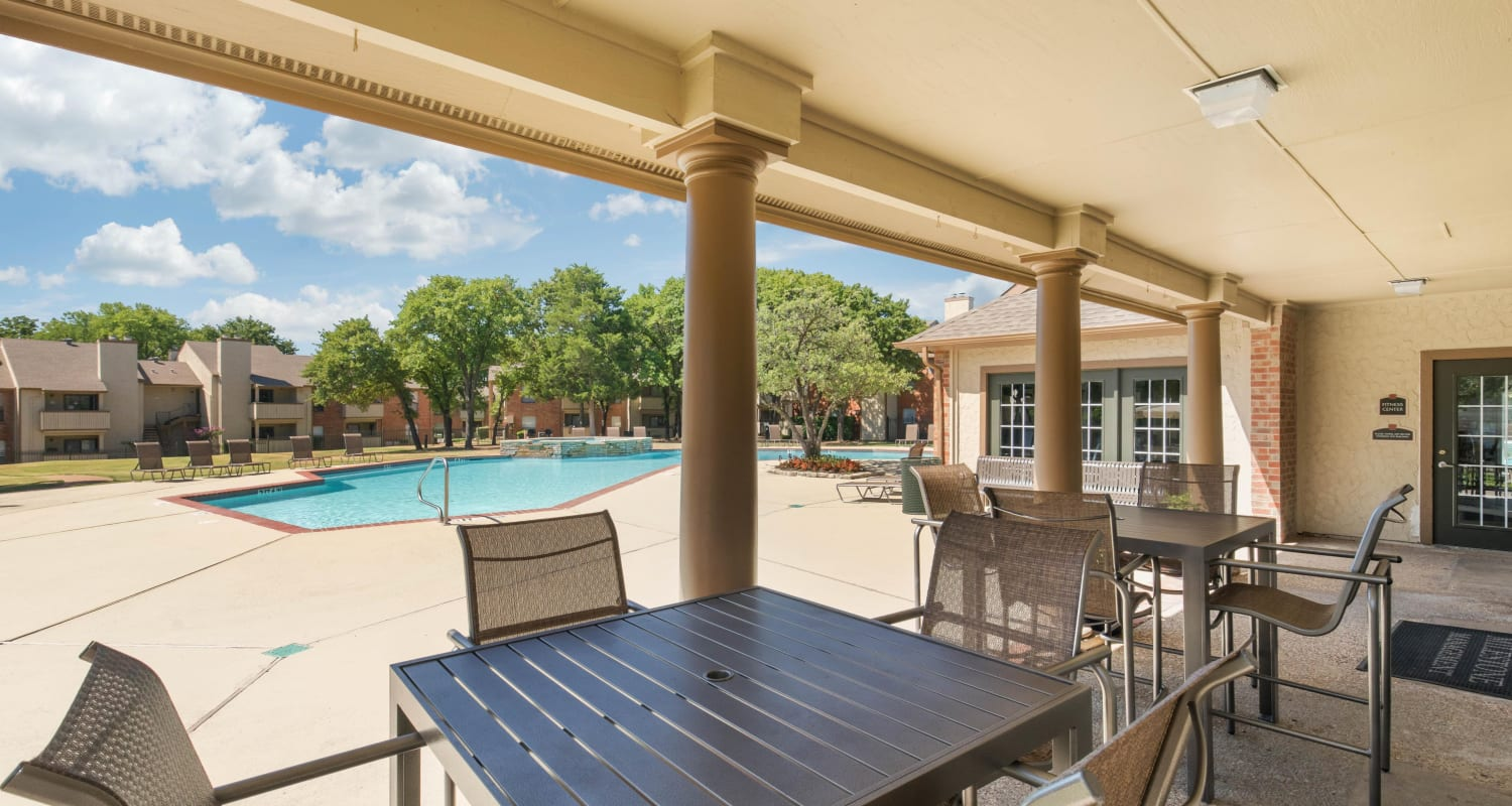 Covered outdoor porch with table and chairs at The Logan in Bedford, Texas