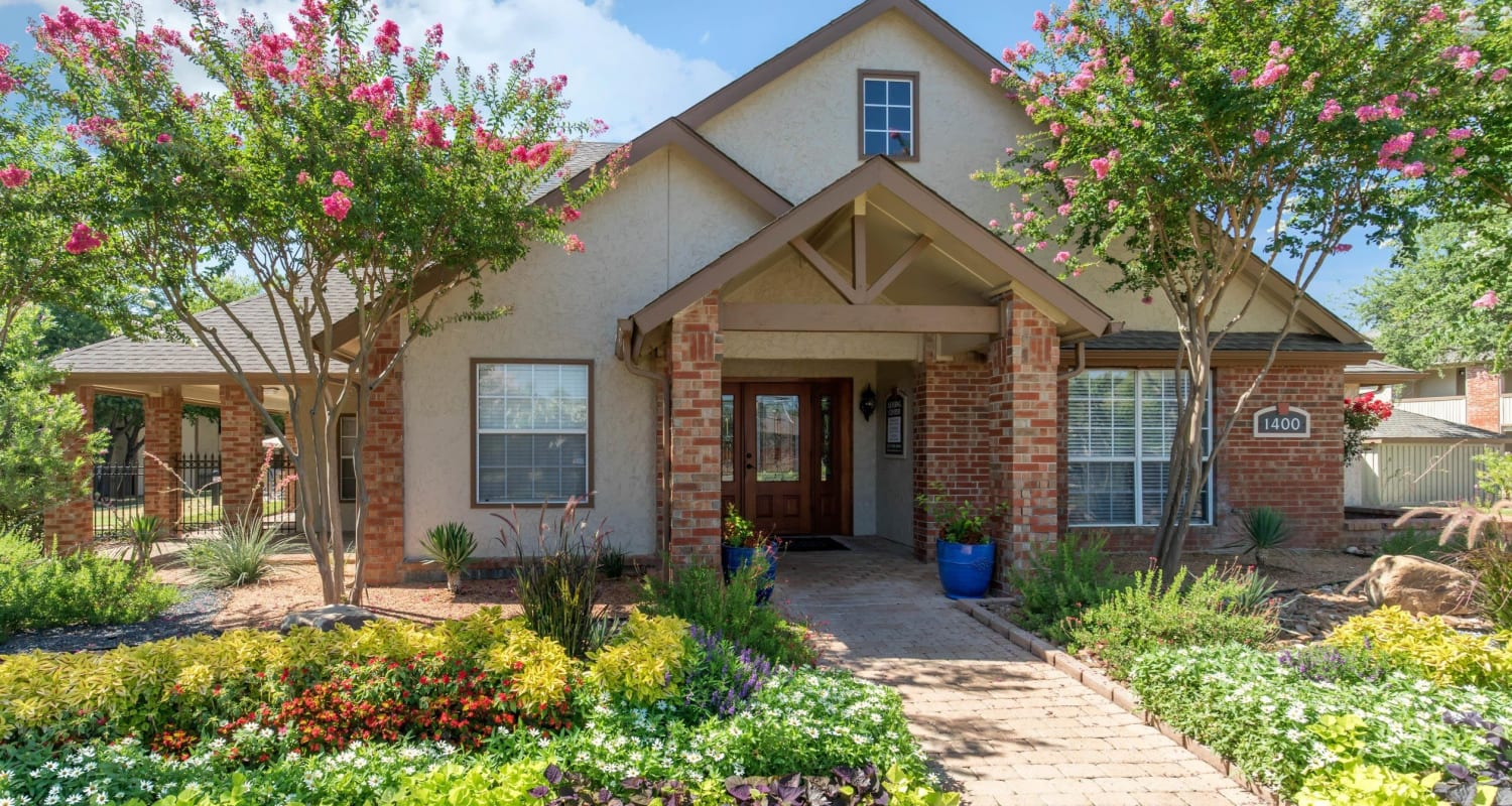 Rustic exterior with a beautifully manicured yard at The Logan in Bedford, Texas