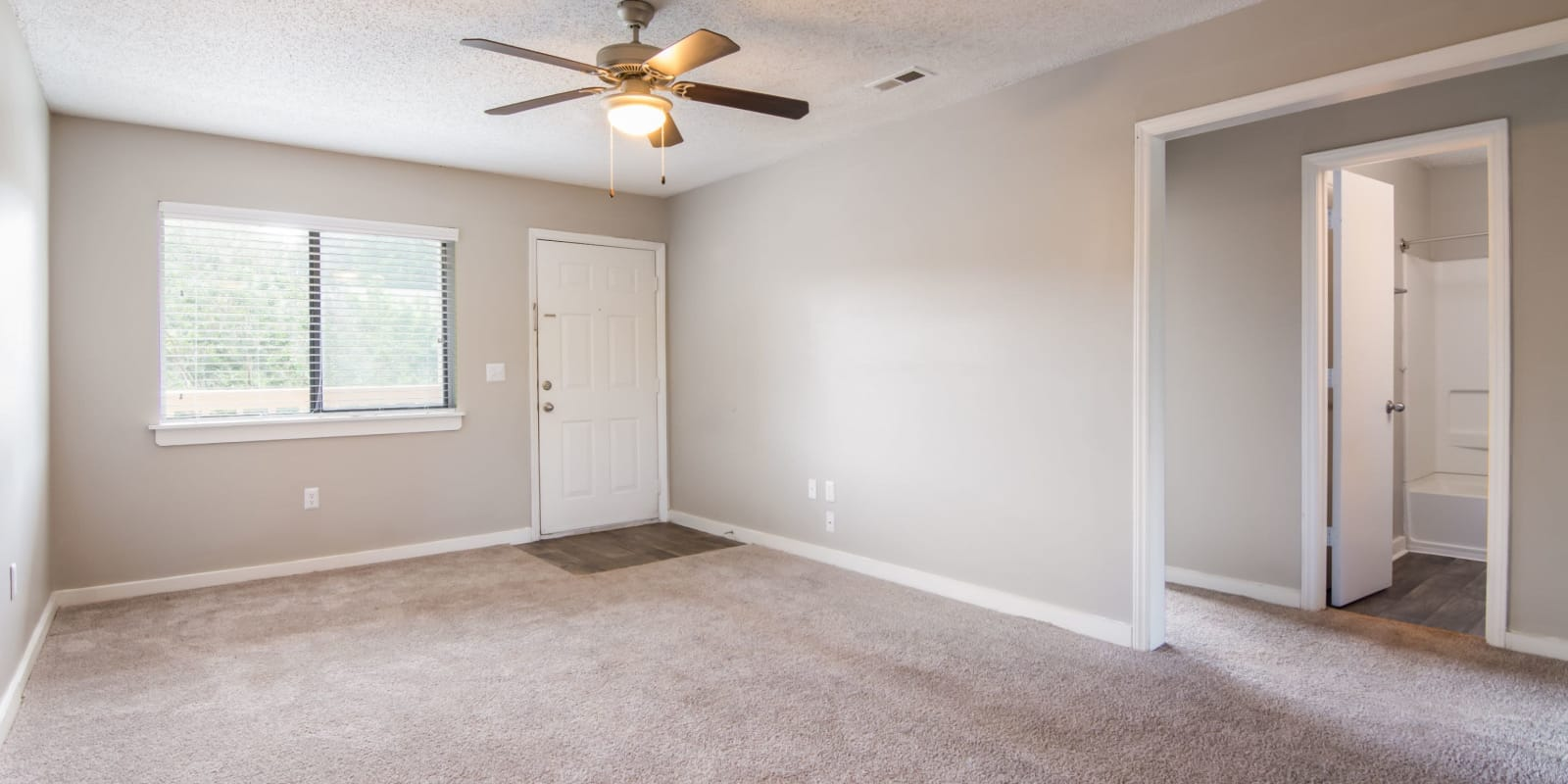 Living room with plush carpeting and a ceiling fan at 1022 West Apartment Homes in Gaffney, South Carolina