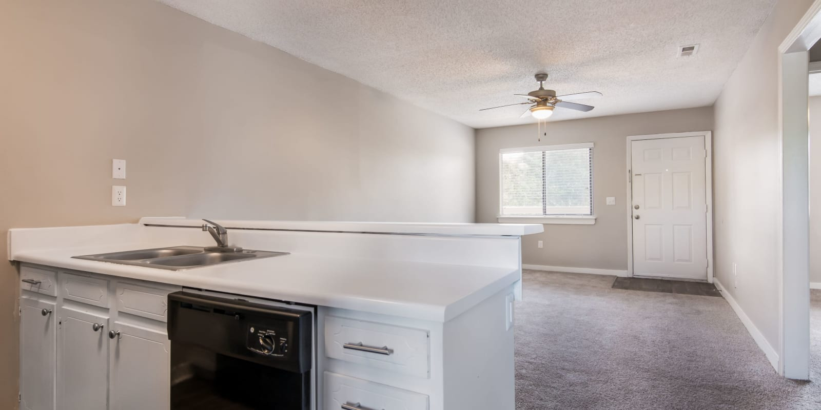 Kitchen overlooking the living room with plush carpeting at 1022 West Apartment Homes in Gaffney, South Carolina