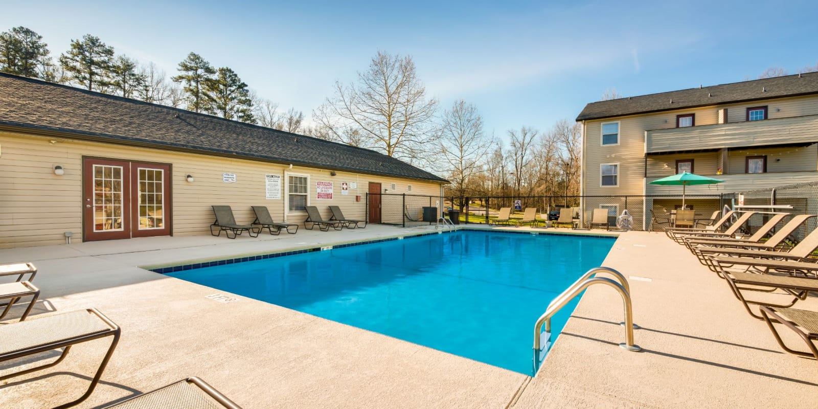 Swimming pool with tables and chairs for poolside picnics at Alexander Station Apartment Homes in Salisbury, North Carolina