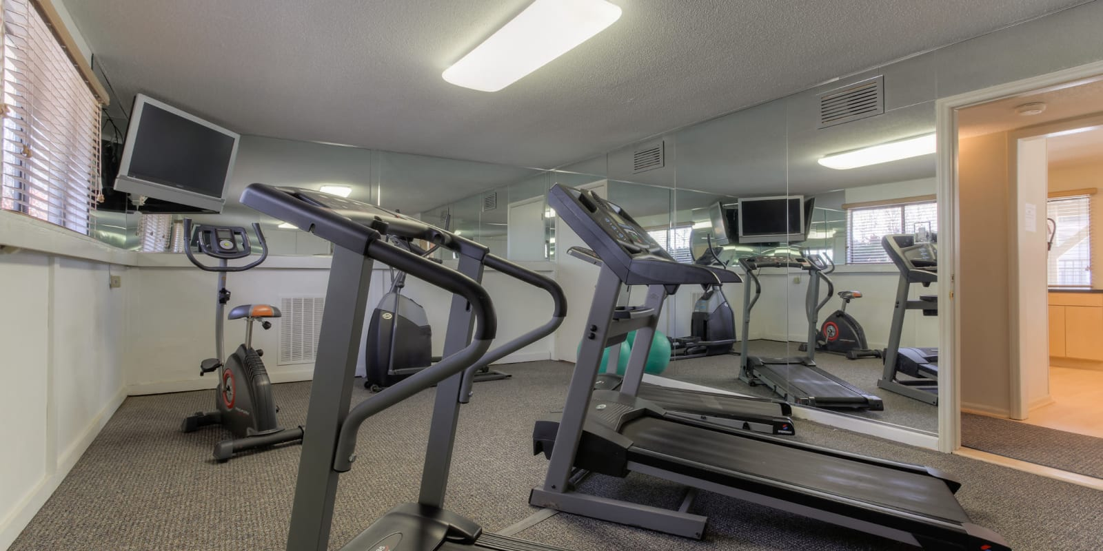 A fitness center with TVs at Enclave at North Point Apartment Homes in Winston Salem, North Carolina