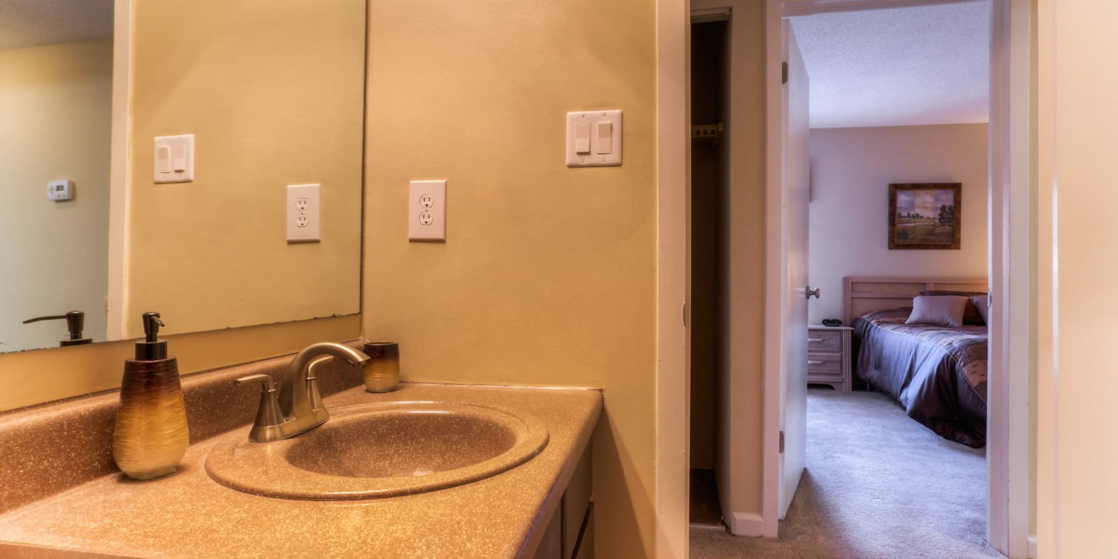 The main bathroom with a large vanity mirror at Enclave at North Point Apartment Homes in Winston Salem, North Carolina