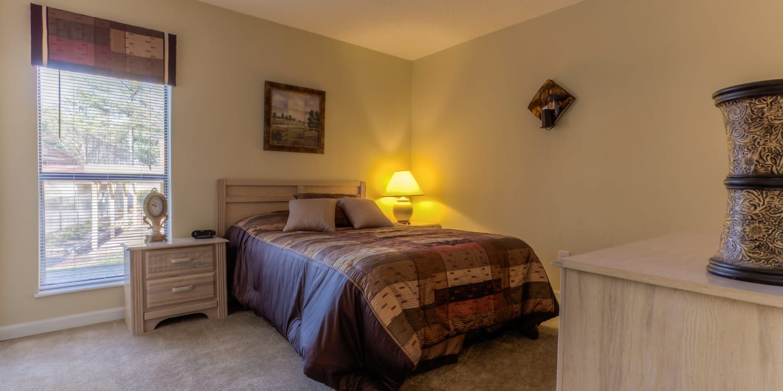 Spacious bedroom with a large window and plush carpeting at Enclave at North Point Apartment Homes in Winston Salem, North Carolina