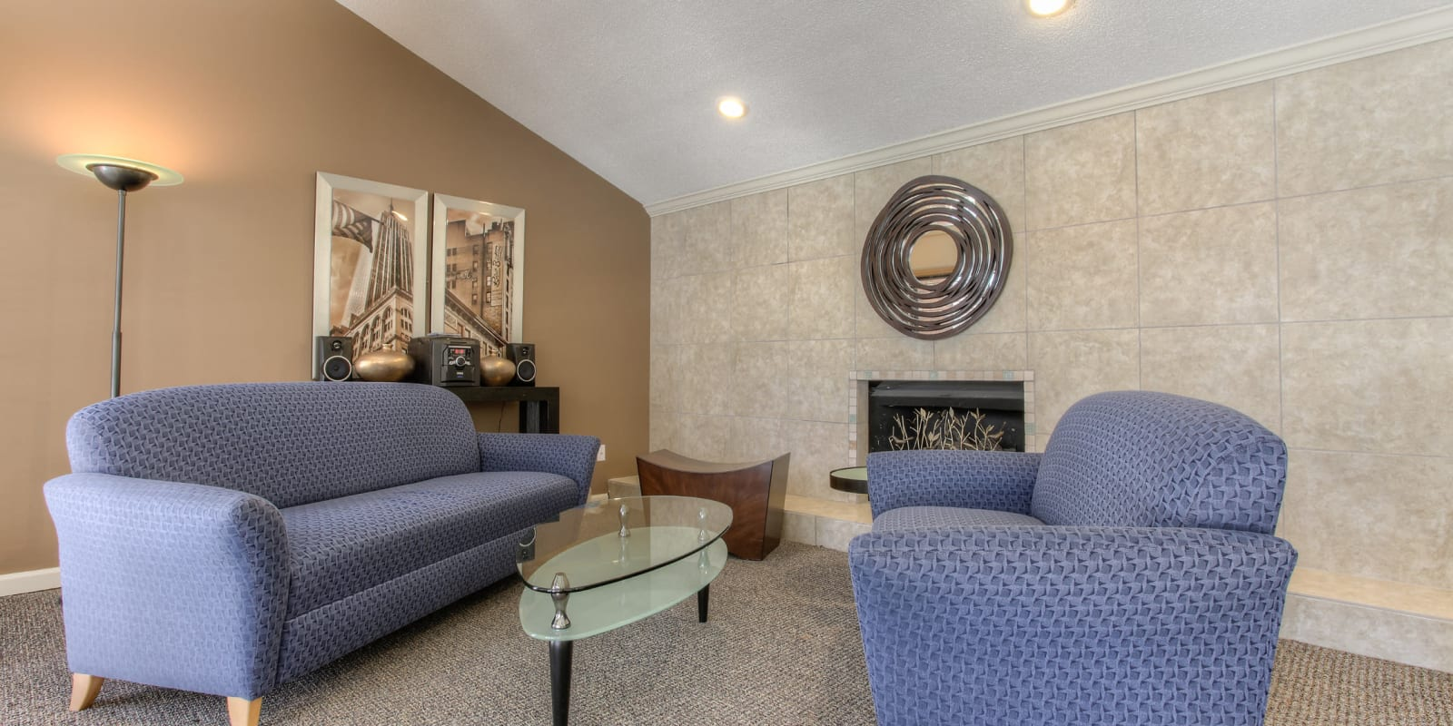 Comfortable clubhouse seating next to a fireplace at Enclave at North Point Apartment Homes in Winston Salem, North Carolina