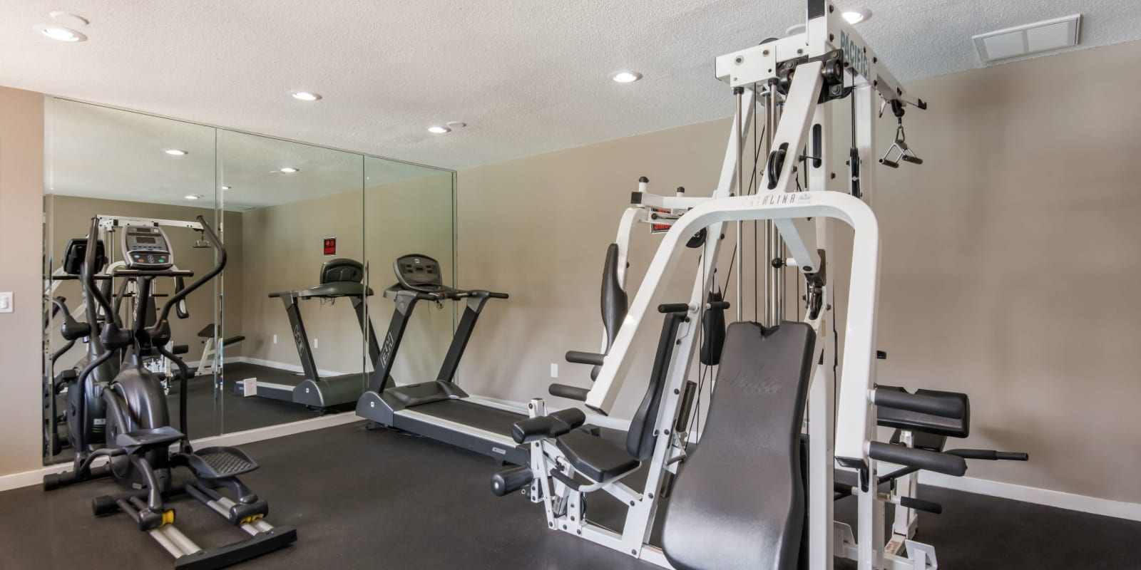 Fitness center with a mirrored-wall at Gable Oaks Apartment Homes in Rock Hill, South Carolina