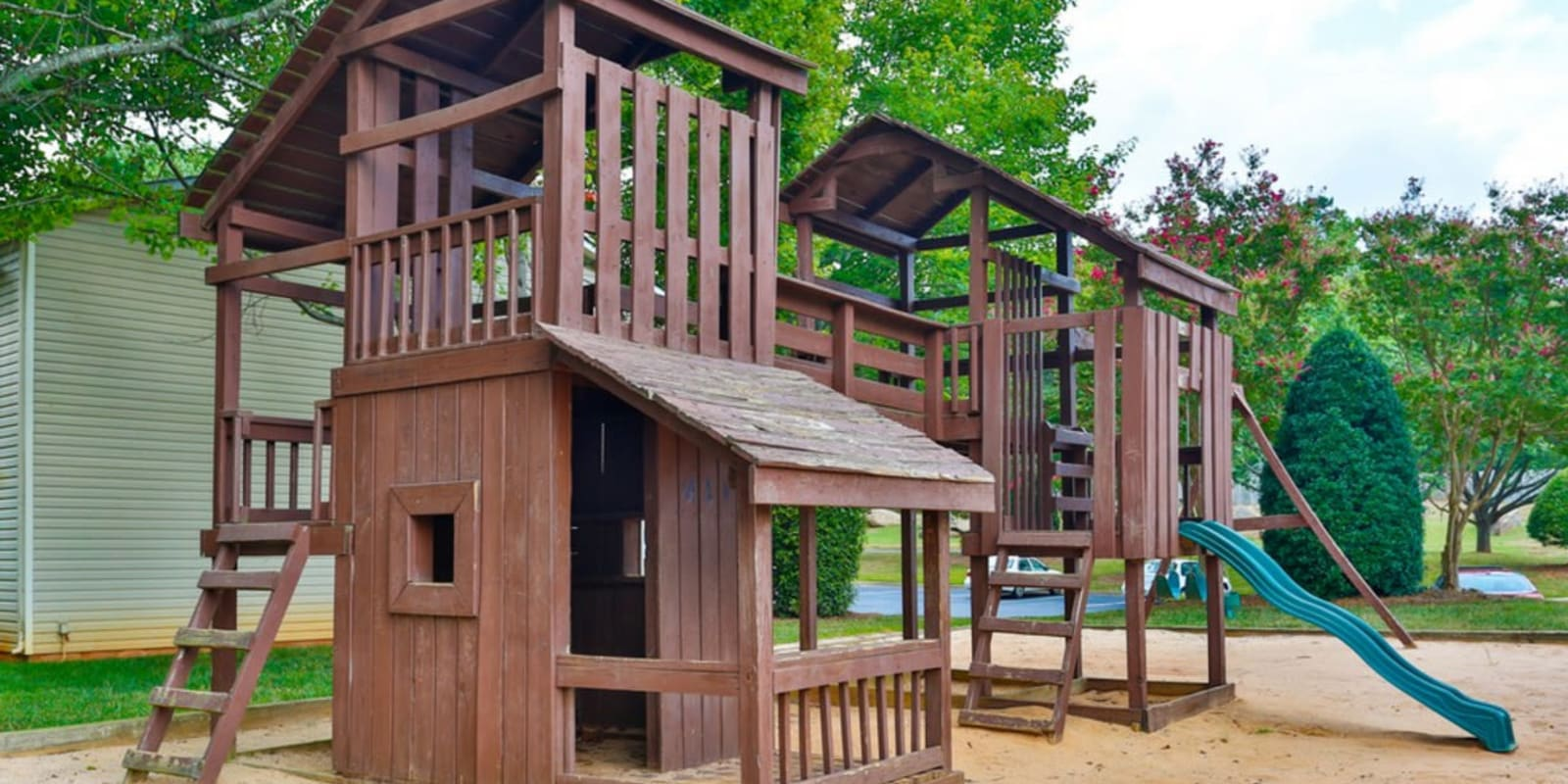 Rustic playground with a slide for resident children at Huntersville Apartment Homes in Huntersville, North Carolina