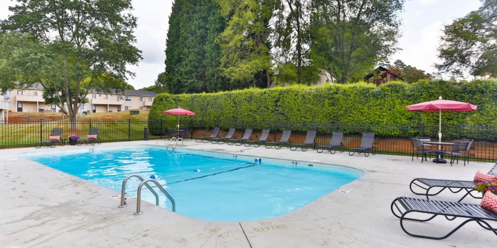 Charming swimming pool with lounge chairs at Huntersville Apartment Homes in Huntersville, North Carolina