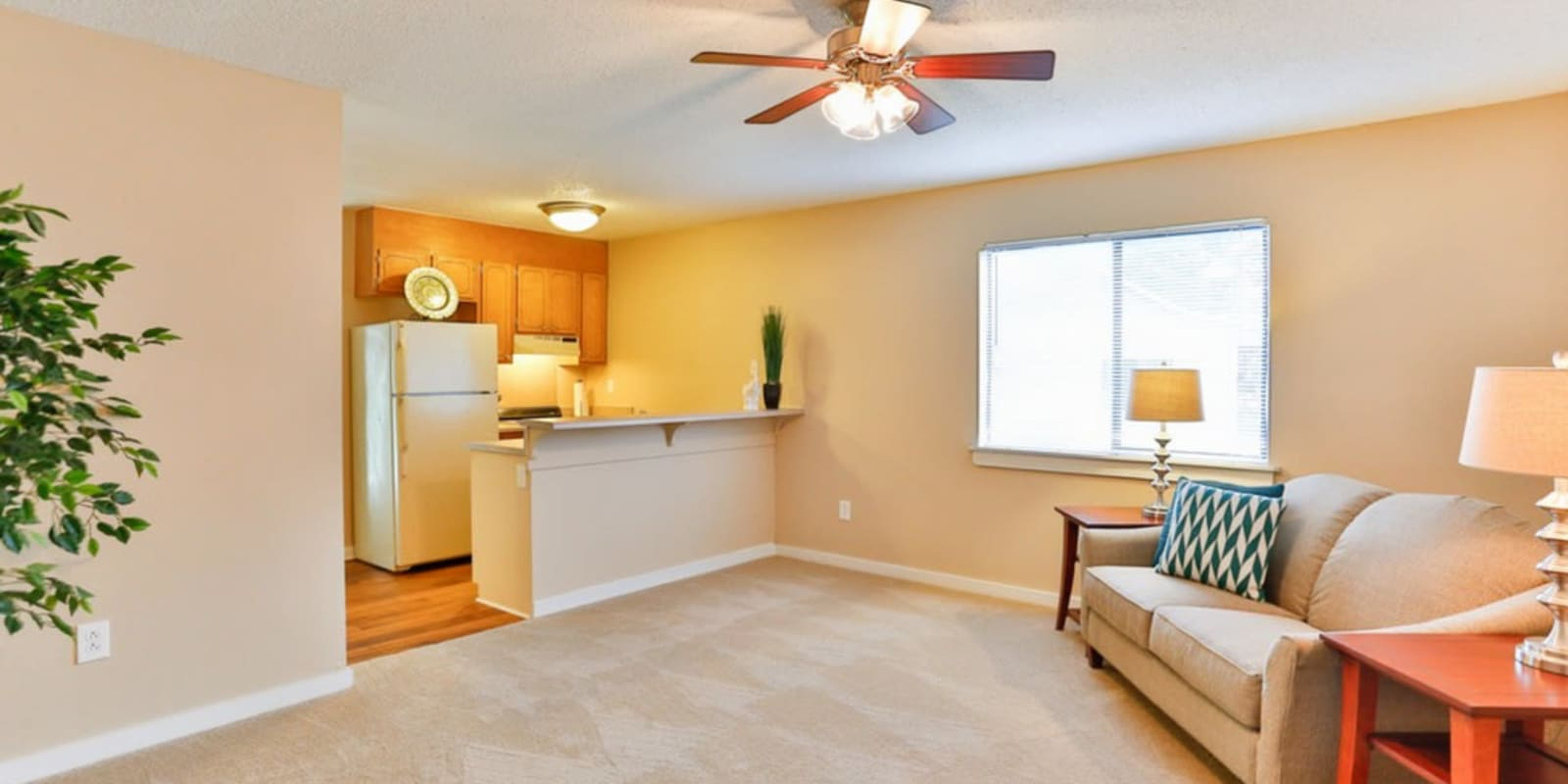 Spacious living room with a ceiling fan at Huntersville Apartment Homes in Huntersville, North Carolina