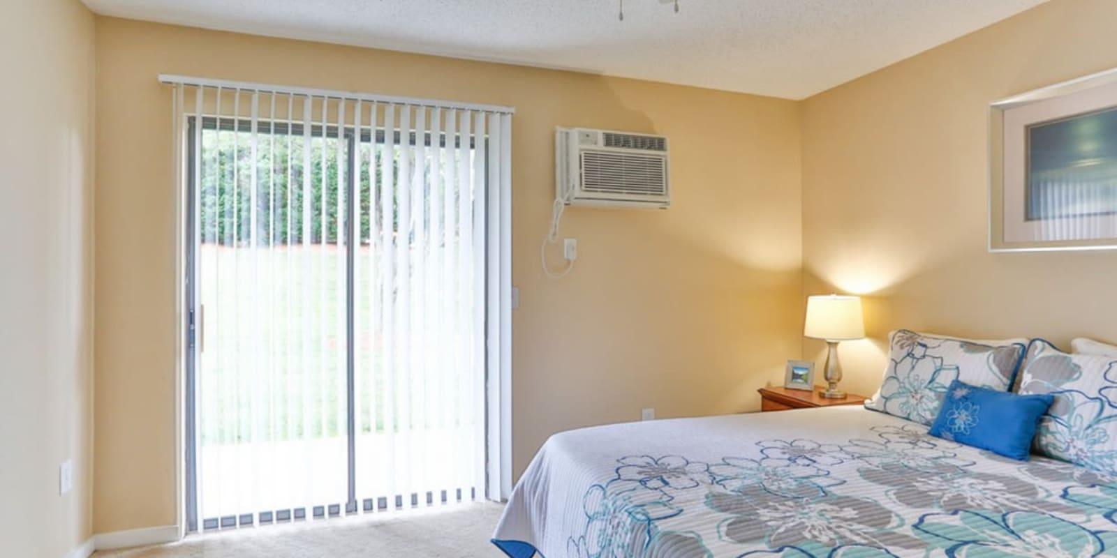 Main bedroom with balcony access at Huntersville Apartment Homes in Huntersville, North Carolina