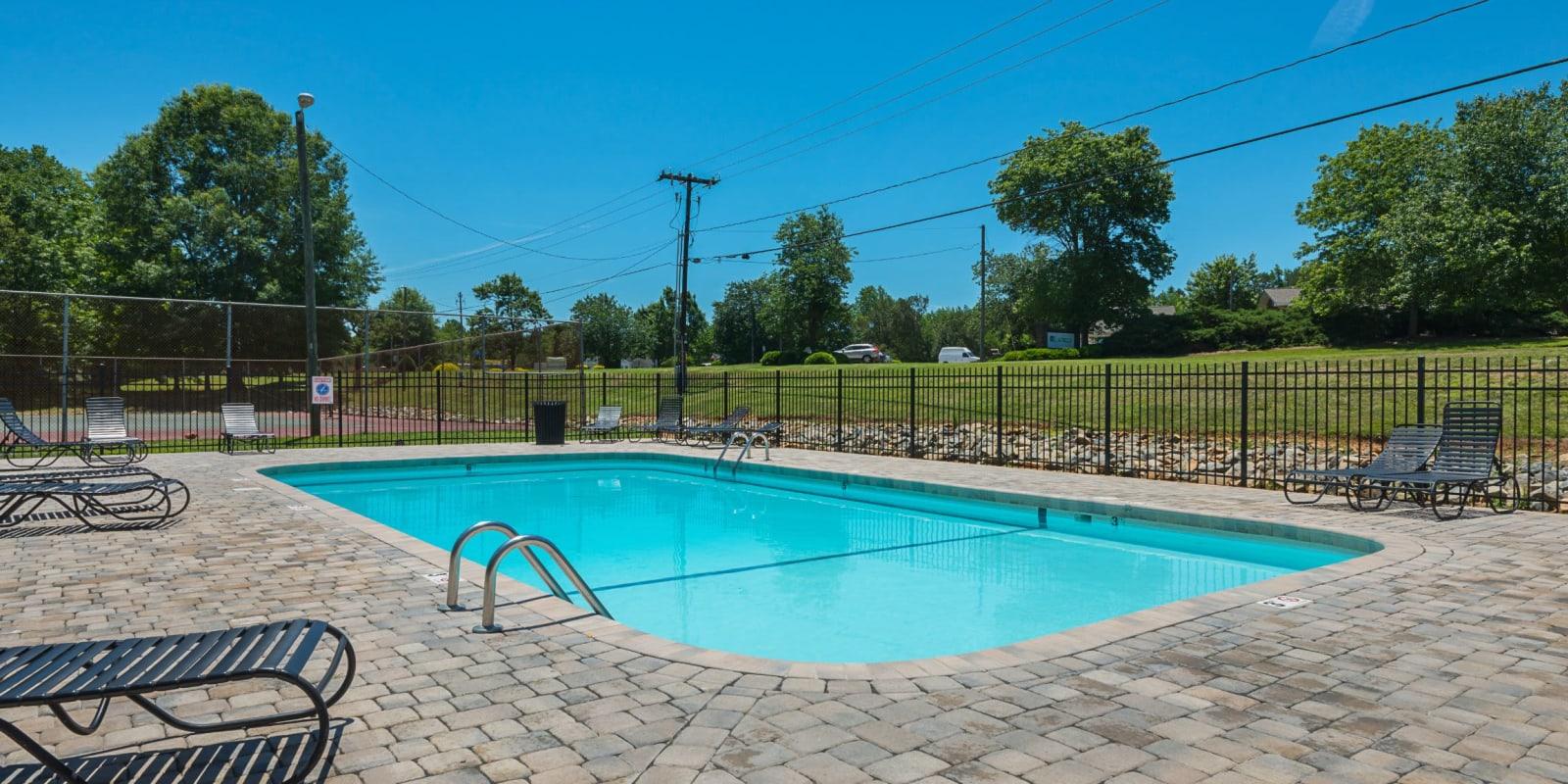 Beautiful swimming pool with lounge chairs at Lakewood Apartment Homes in Salisbury, North Carolina