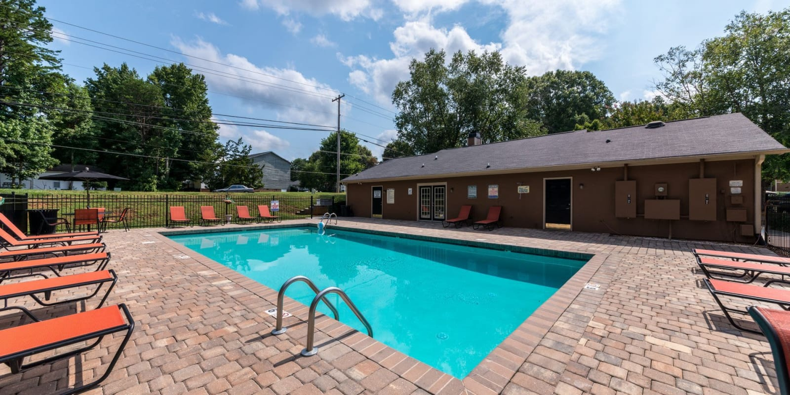 Swimming pool with a large sundeck and lounge chairs at Waters Edge Apartment Homes in Concord, North Carolina
