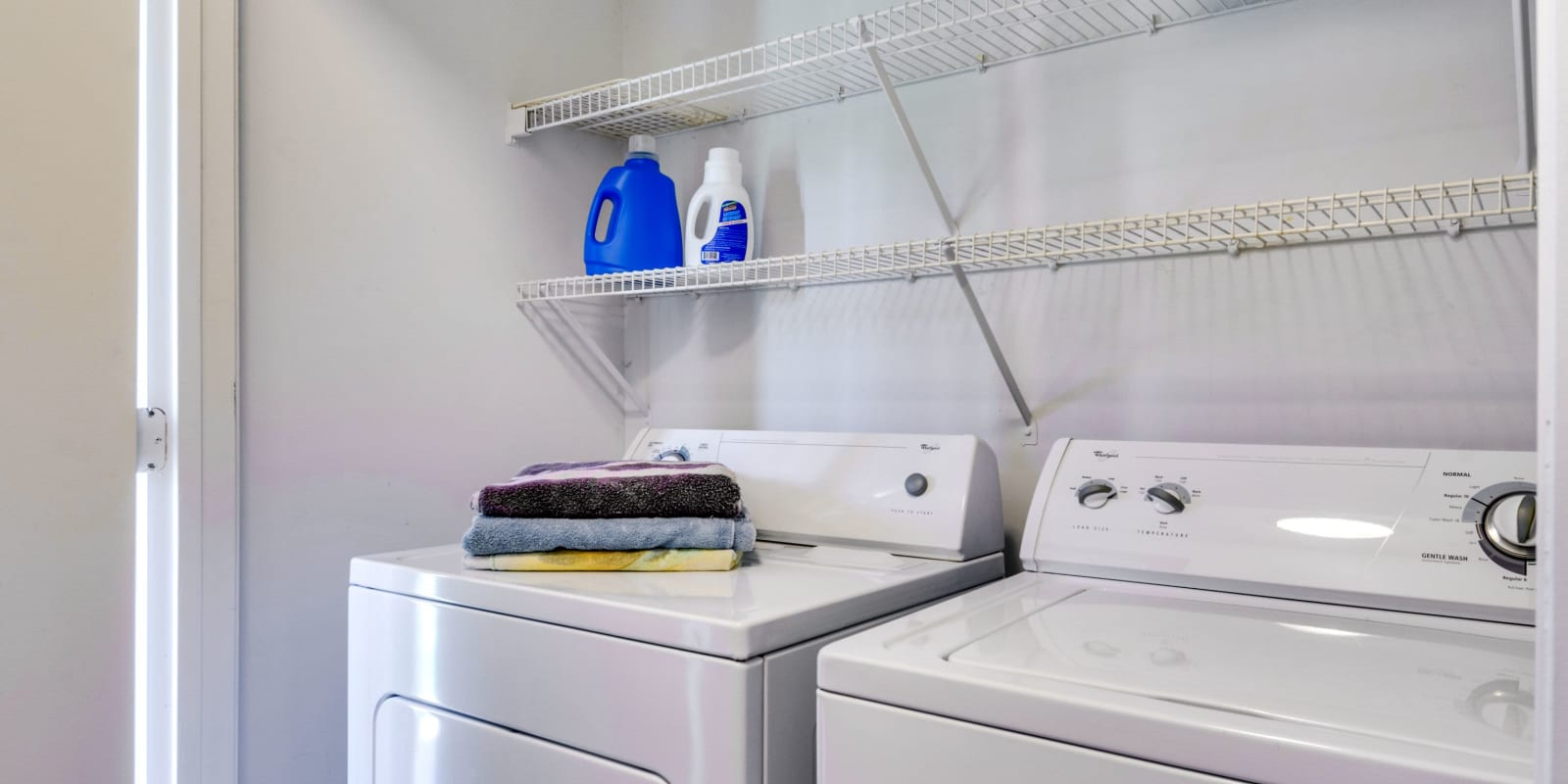 Washer and dryer room with shelving at Woodbrook Apartment Homes in Monroe, North Carolina