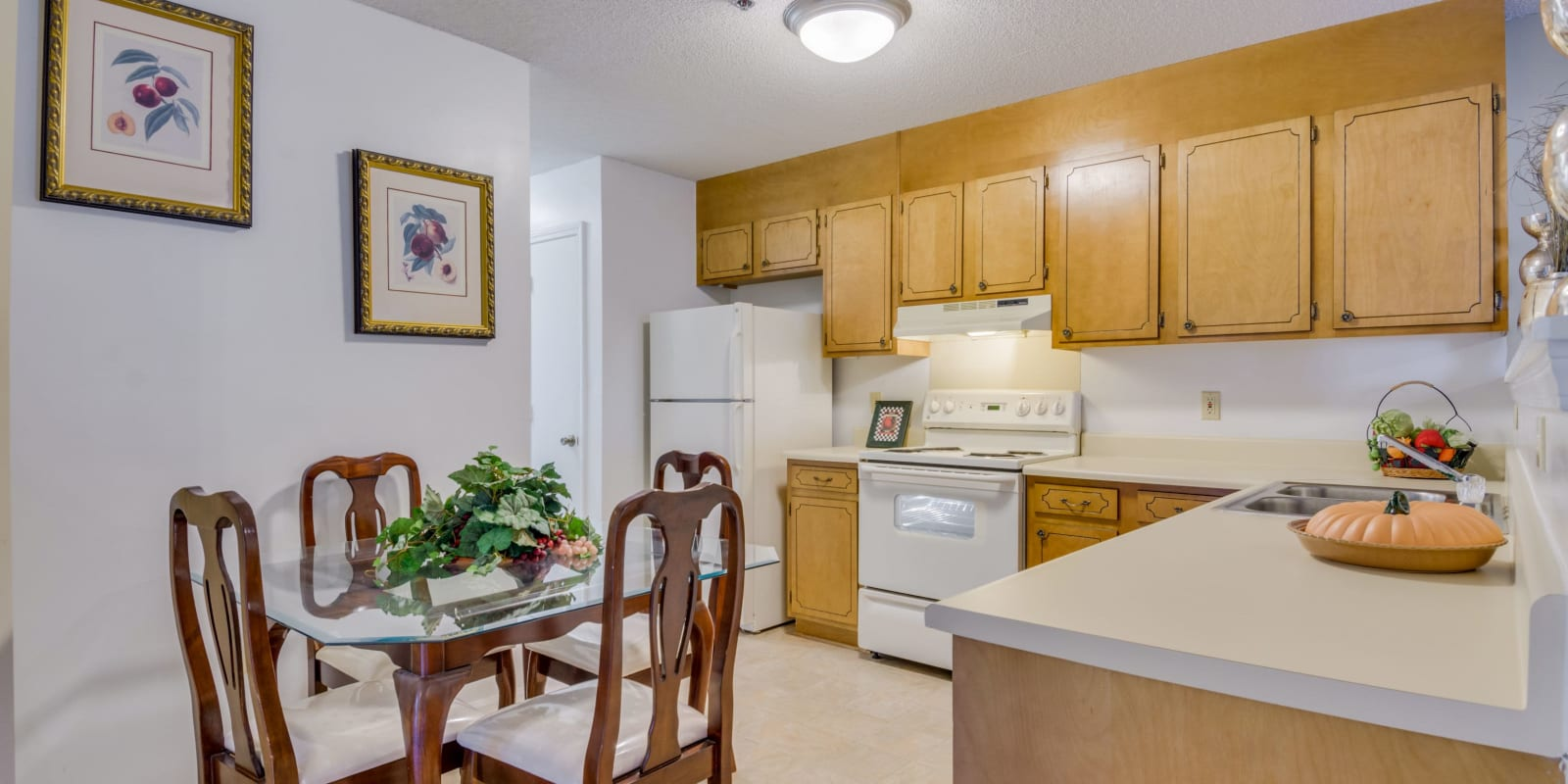 Kitchen with white appliances at Woodbrook Apartment Homes in Monroe, North Carolina