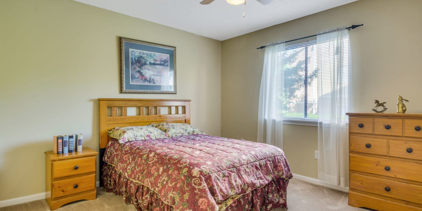 Spacious bedroom with a large window and plush carpeting at Woodbrook Apartment Homes in Monroe, North Carolina