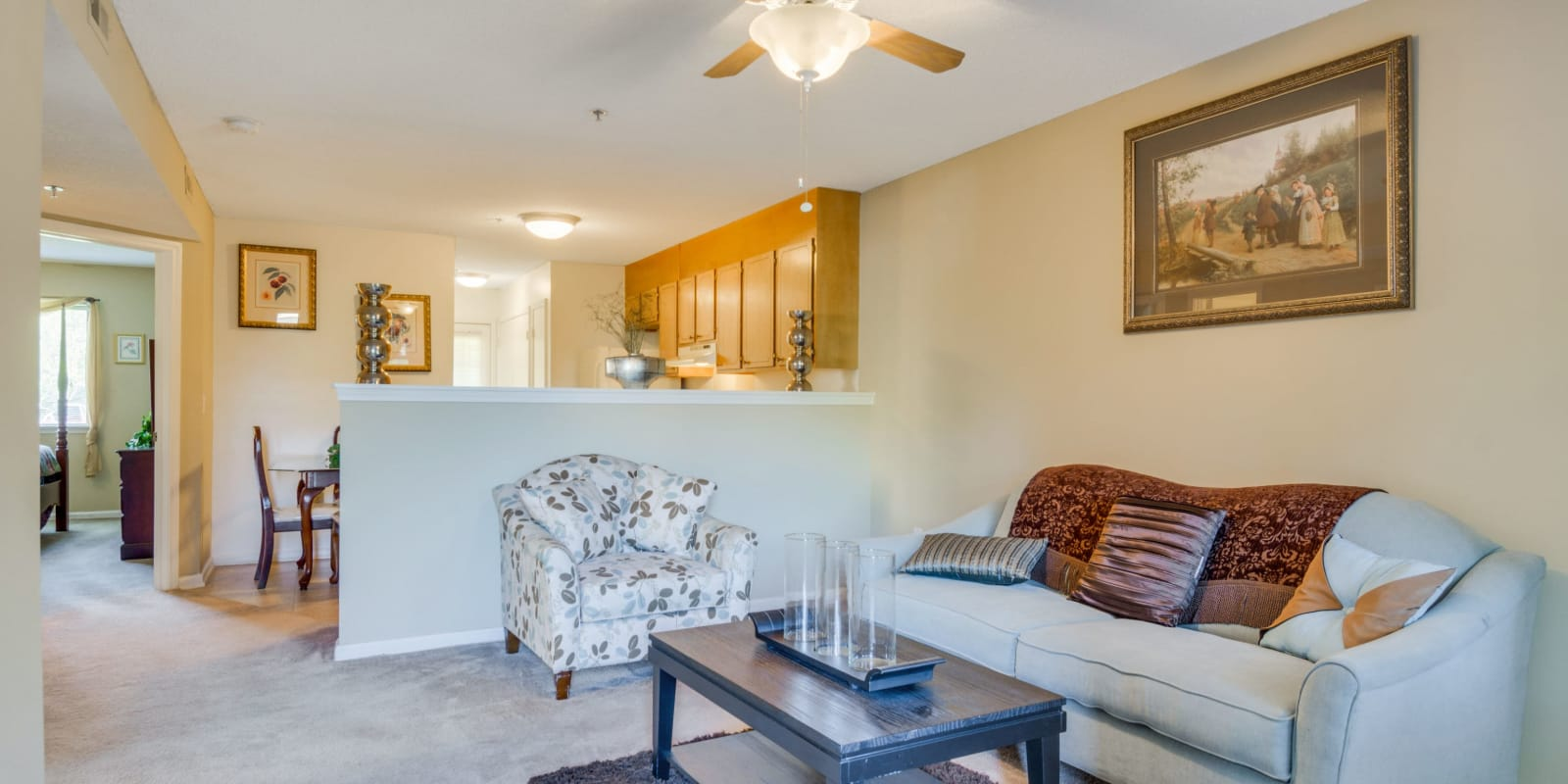 A living room with a ceiling fan at Woodbrook Apartment Homes in Monroe, North Carolina