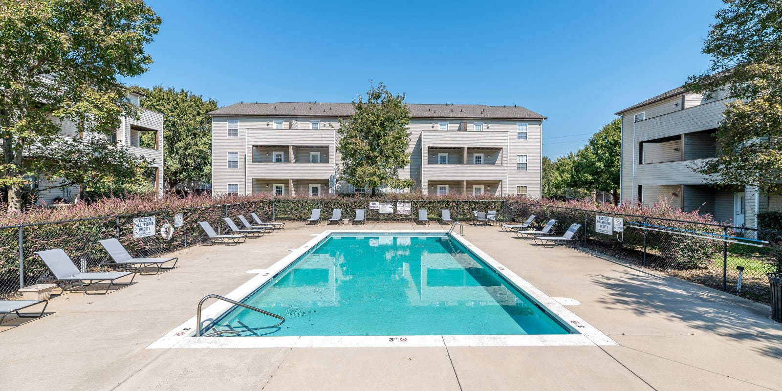 Swimming pool with poolside lounge chairs at The Village at Brierfield Apartment Homes in Charlotte, North Carolina