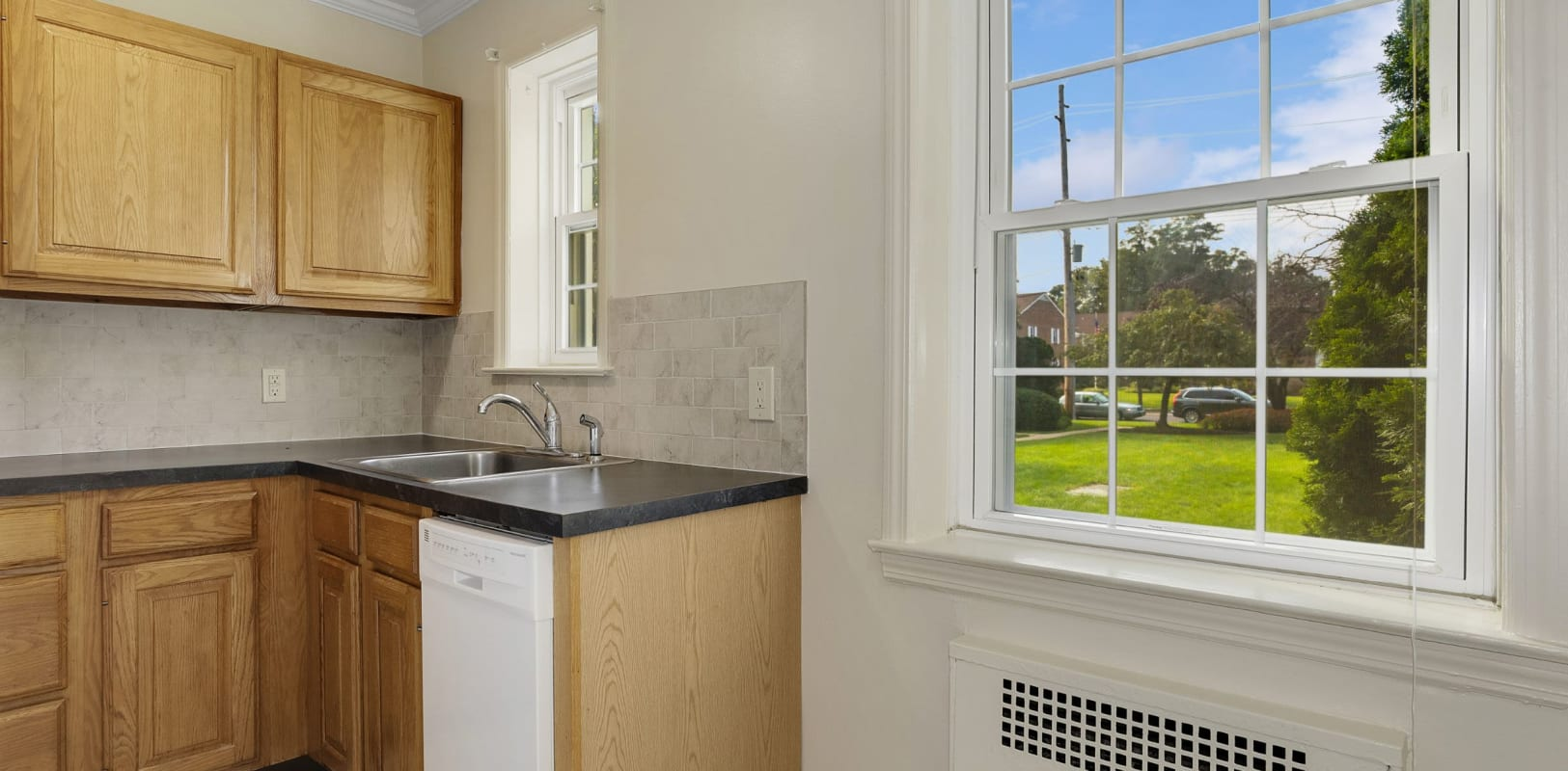 Kitchen with a large window at Mayflower Apartments in Ridgewood, New Jersey