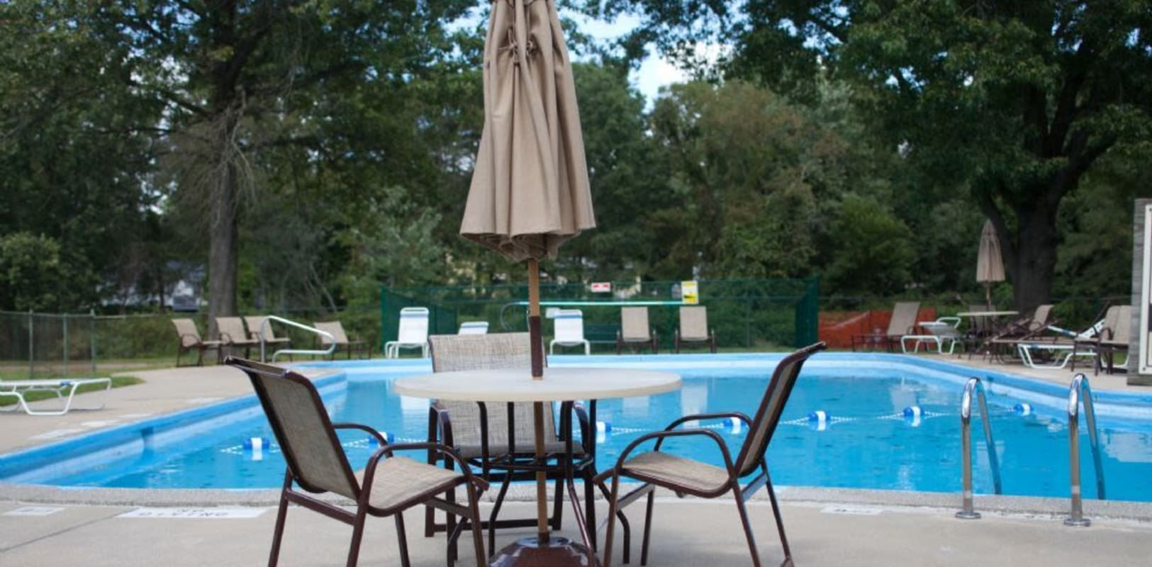 Sparkling swimming pool with patio seating at Brookwood Gardens in East Windsor, New Jersey