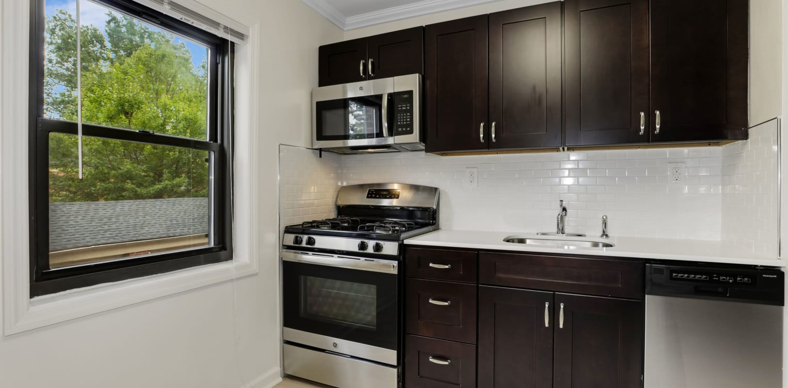 Kitchen with plenty of cabinet space and a large window at Continental Gardens in River Edge, New Jersey