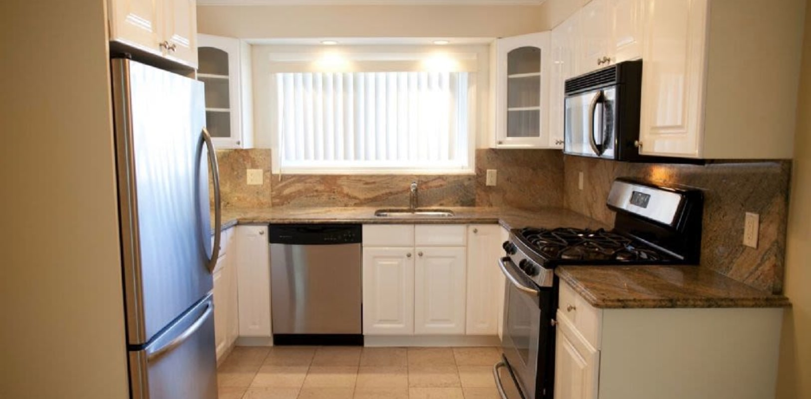 Kitchen with stainless steel appliances at Cottage Place Apartments in Long Branch, New Jersey