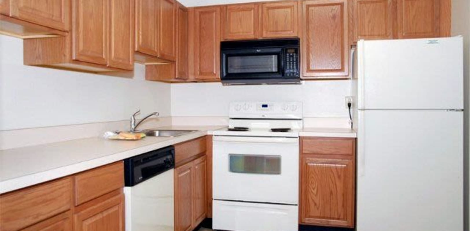 Apartment kitchen with wood style cabinets and white appliances in Whitehall, {location_state_name}} at Lehigh Valley
