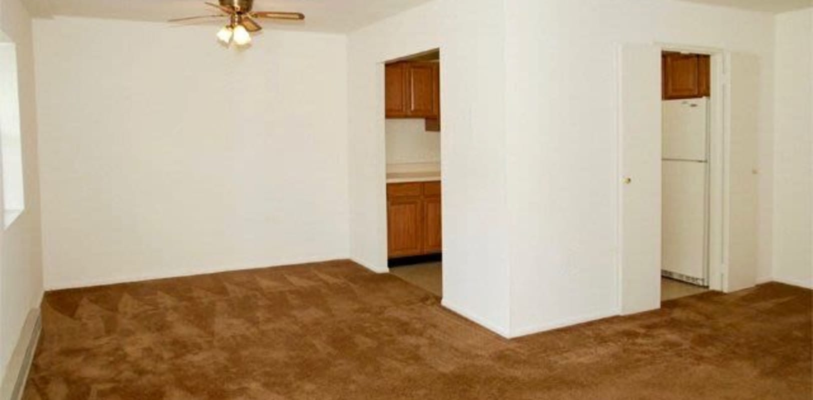 Apartment living room with white walls and wood style floors at Lehigh Valley in Whitehall, {location_state_name}}