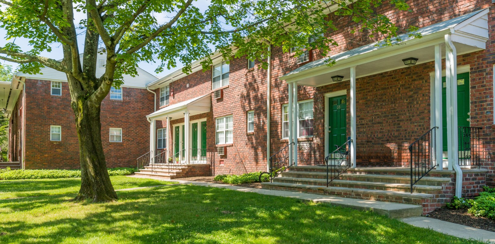 Nice shaded lawn next to brick building at Nottingham Manor in Montvale, New Jersey