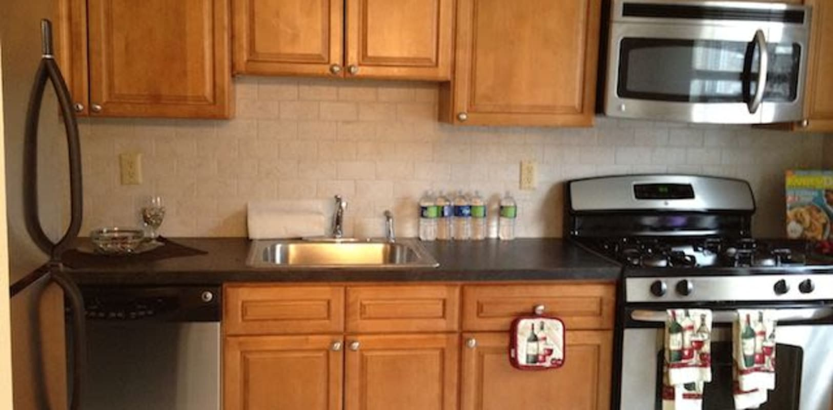 Full kitchen with new appliances and light wood cabinets at Park Lane Apartments in Little Falls, New Jersey