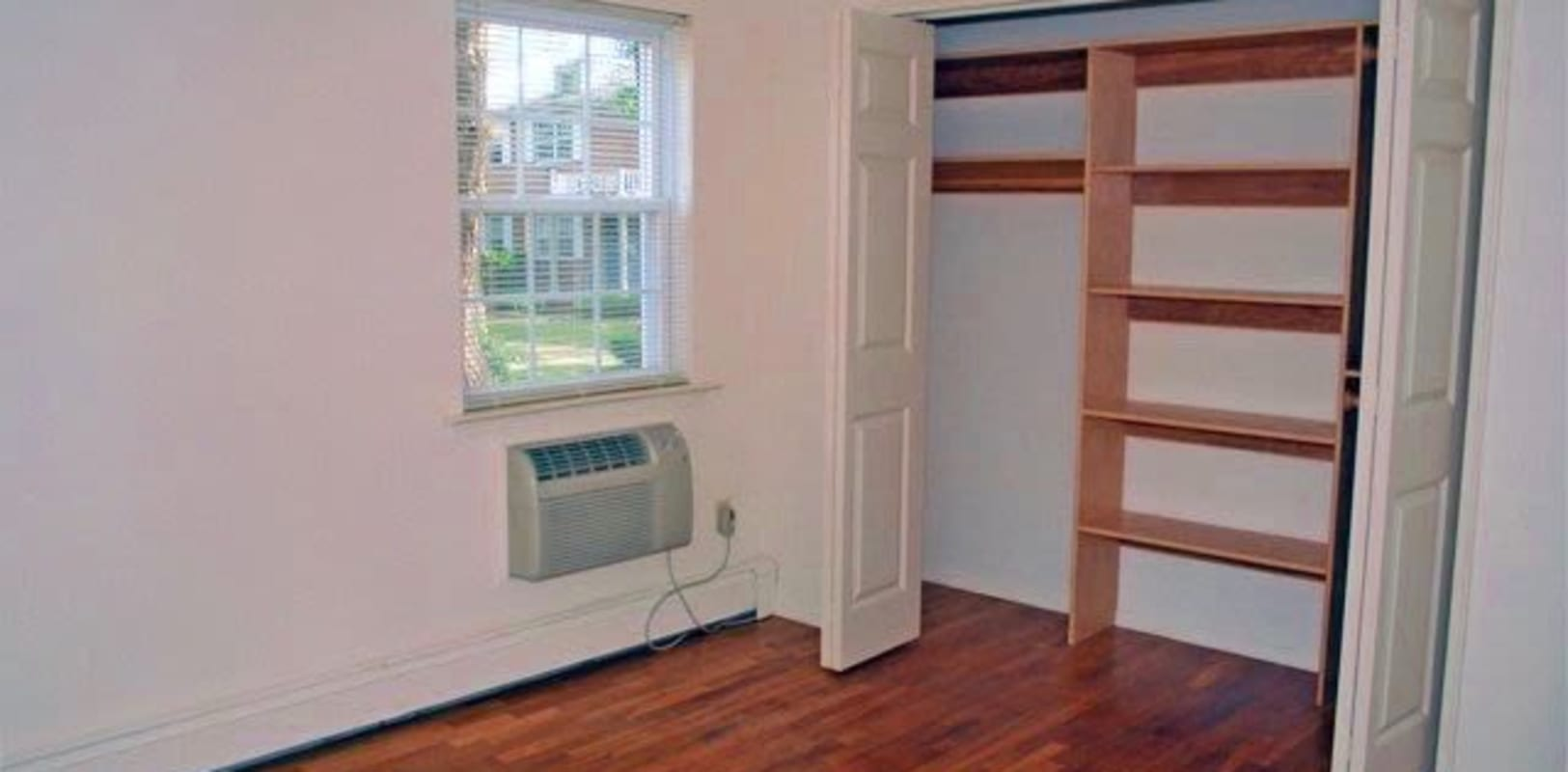 Bedroom with air conditioning unit and wooden shelves in closet for storage at Park Lane Apartments in Little Falls, New Jersey